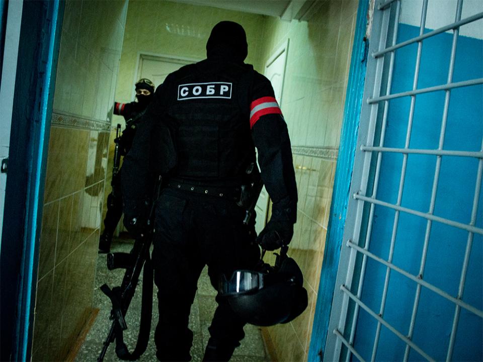 Сотрудники подразделения специального назначения занимают позиции в помещениях на первых этажах здания, в котором укрепились условные террористы
