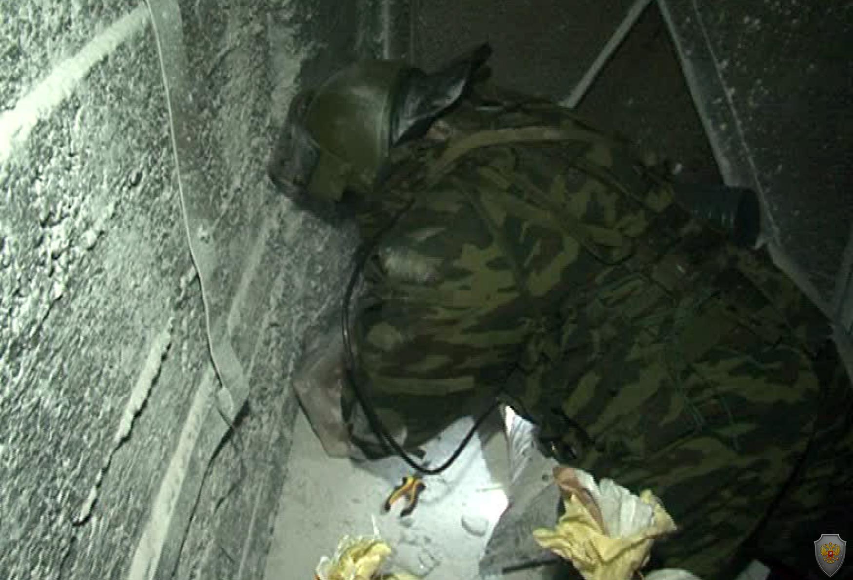 Сотрудник группы ликвидации угрозы взрыва (ОМОН) осматривает СВУ